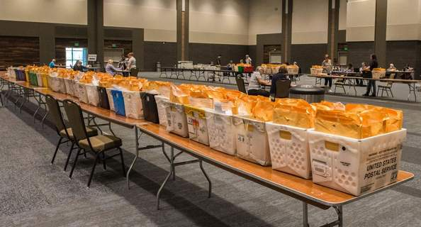FILEBins of mail-in ballots line a table during counting at Memorial Coliseum in June.