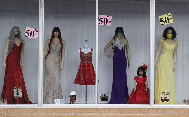 Associated Press Masked mannequins model discounted dresses in McAllen, Texas. Consumers spent more in June, federal data shows.