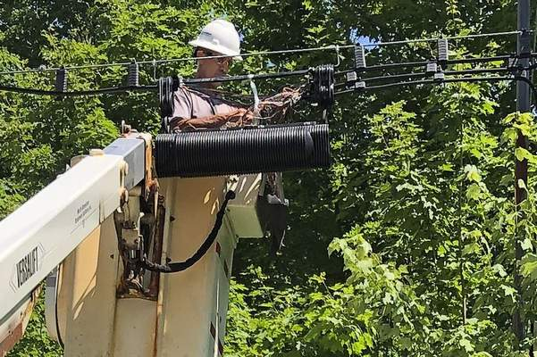 A Consolidated Communications technician works on a line used to provide broadband internet service in a rural area on Wednesday, July 29, 2020, in Stowe, Vt. (AP Photo/Wilson Ring)