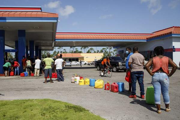 Residents wait in line to fill their containers with gasoline before the arrival of Hurricane Isaias in Freeport, Grand Bahama, Bahamas, Friday, July 31, 2020. (AP Photo/Tim Aylen)