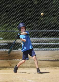 Katie Fyfe | The Journal Gazette Liam Haberman, 9, practices his batting skills with his brother Judah Haberman, 11, and his father Matt Haberman, not pictured, at the Foster Park baseball fields on Wednesday, July 29th, 2020.