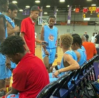 Courtesy photo Kareem Hunter Sr., standing in red, speaks to his Fort Wayne Unlimited team early on during a recent game at Harlan Christian Center. Playing its first year, the team is off to a 2-1 start.
