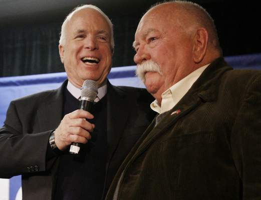 FILE - In this Jan. 4, 2008, file photo, Republican presidential hopeful, Sen. John McCain, R-Ariz., left, introduces actor, Wilford Brimley, after making a reference to fellow Republican presidential hopeful, former Arkansas Gov. Mike Huckabee, campaigning with actor Chuck Norris, as McCain makes a campaign stop at Hudson Veterans of Foreign Wars Post 5791, in Hudson, N.H. (AP Photo/Charles Dharapak, File)