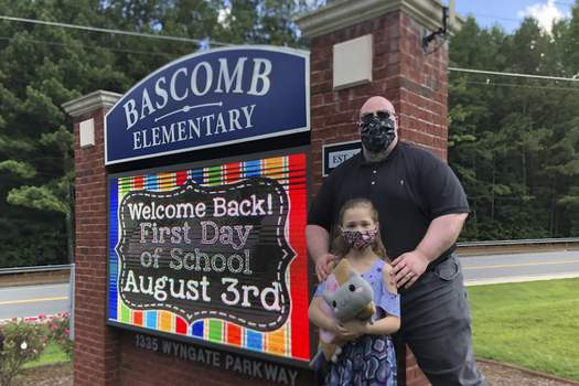 Virus Outbreak John Barrett and his daughter Autumn pose for photos outside Bascomb Elementary School in Woodstock, Ga., Thursday, July 23, 2020. (AP Photo/Jeff Amy) (Jeff Amy STF)