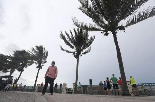 Tropical Weather Florida People gather to watch the strong waves on the beach as palm trees sway in the wind, Sunday, Aug. 2, 2020, in Vero Beach, Fla. (AP Photo/Wilfredo Lee) (Wilfredo Lee STF)