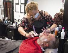 Photos by Michelle Davies | The Journal Gazette Dan Wirt of Monroeville gets a shave from Anna Burnside at her New Haven business, Anna's Barber Shop.
