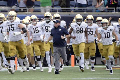 ACC Notre Dame Football FILE - In this Dec. 28, 2019, file photo, Notre Dame head coach Brian Kelly, center, runs onto the field with his players before the Camping World Bowl NCAA college football game against Iowa State in Orlando, Fla. The Atlantic Coast Conference and Notre Dame are considering whether the Fighting Irish will give up their treasured football independence for the 2020 season play as a member of the league. (AP Photo/Phelan M. Ebenhack, File) (Phelan M. Ebenhack FRE)
