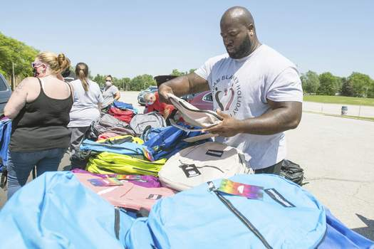 Michelle Davies | The Journal Gazette Adam Blakey, with Adam Blakey Holiday Foundation, sorts through book bags at Saturday's giveaway at Wayne High School.