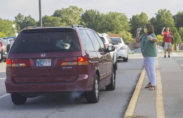 Michelle Davies | The Journal Gazette Lincoln Elementary School teachers Kimberly Fransen, front, and Gilbert Morlan wave cars through the drop-off line Thursday morning on the first day of classes.