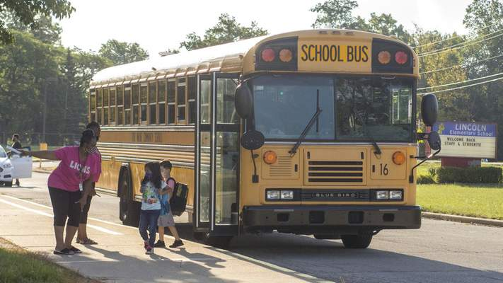 Michelle Davies | The Journal Gazette Kim Tanner, case manager for Lincoln Elementary School, along with Felicia Williams, administrative assistant, directs children where to go as they arrive for the first day of school Thursday.