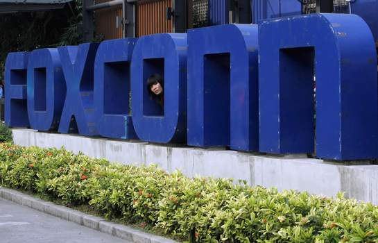 Foxconn University Pledge FILE - In this May 27, 2010 file photo, a worker looks out through the logo at the entrance of the Foxconn complex in the southern Chinese city of Shenzhen. The University of Wisconsin-Madison has received less than 1% of the money that Taiwan-based Foxconn Technology Group pledged to it two years ago amid the electronics giant's expansion plans in Wisconsin. In August 2018, Foxconn committed $100 million to the university to help fund an engineering building and for company-related research. (AP Photo/Kin Cheung, File) (Kin Cheung