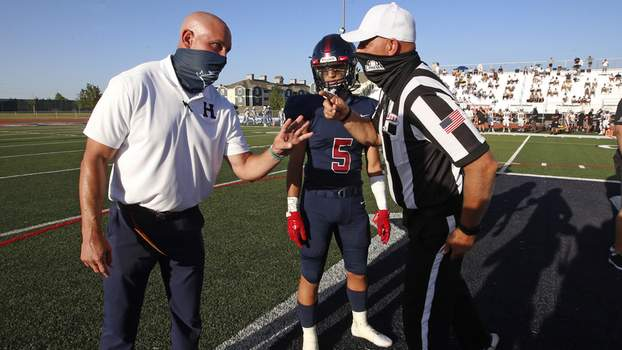 Virus Outbreak High School Sports Football Herriman coach Dustin Pearce and Brock Hollingsworth (5) speak with an official during the coin toss before a high school football against Davis on Thursday, Aug. 13, 2020, in Herriman, Utah. Utah is among the states going forward with high school football this fall despite concerns about the ongoing COVID-19 pandemic that led other states and many college football conferences to postpone games in hopes of instead playing in the spring. (AP Photo/Rick Bowmer) (Rick Bowmer