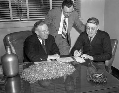 April 1, 1948: Ed Adreon, right, brought 8,000 dimes to Rousseau Bros. Auto Agency to buy a car. Here, he closes the deal with Bert Rousseau, left, and Richard Rousseau. (Journal Gazette file photo)