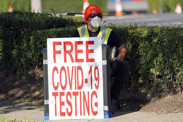 Associated Press Ahealth care worker sits at the entrance to a free COVID-19 testing site last week in Houston. Health officials changed the guidance on virus testing.