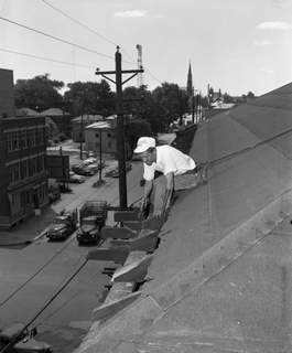 June 1954: Workman Elbert Colwell saws through aged beams on the roof of the Fort Wayne Rescue Home and Mission, 343 E. Columbia St. (Journal Gazette file photo)