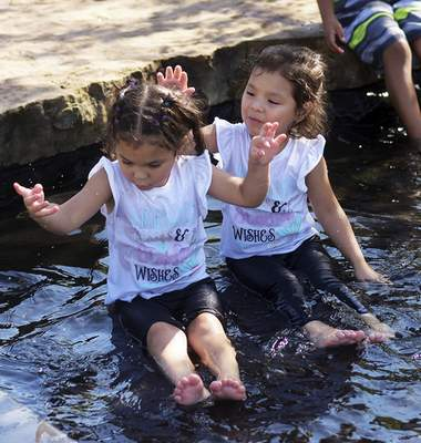 Katie Fyfe | The Journal Gazette Twin sisters Nicole and Zoe Garcia, 4, left to right, cool off in the Doermer Kids' Canal at Promenade Park on Monday, August 31st, 2020.