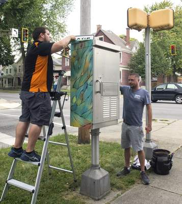 Michelle Davies | The Journal Gazette Nate Roberts, right, and Zack Fritts, left, with Paint the Town Graphics, work on installing a wrap to a traffic box Tuesday morning at the intersection of Van Buren Street and West Washington Boulevard Tuesday morning. The wrap, one of 5 commissioned by the West Central neighborhood and designed by different artists.