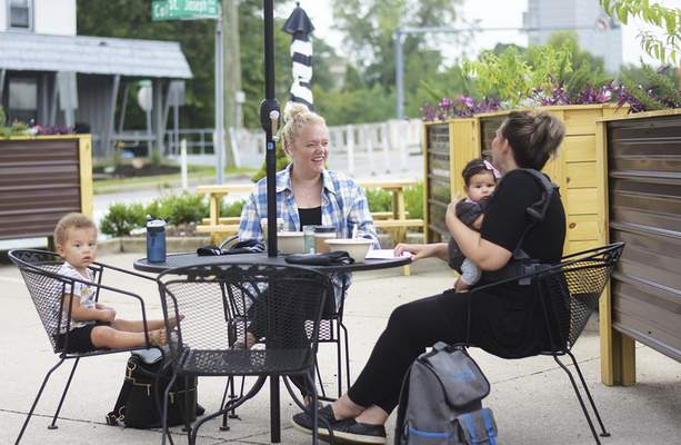 Katie Fyfe | The Journal Gazette  Remington Sheehan, 20 months, Aletha Sheehan, Josephine Reuille, 4 months, and Rachael Reuille, left to right, meet up for a coffee at the Conjure Coffee patio on Wednesday, September 2nd, 2020.