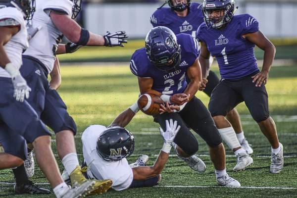 Mike Moore | The Journal Gazette Norwell defensive back Bo Morgan forces a fumble against Leo running back Carson Hoeppner in the second quarter against at Leo High School on Friday.