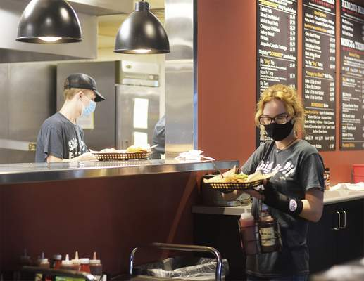 Server Madison McCoy grabs food to serve at Shigs In Pit BBQ & Brew on Maplecrest Road.
