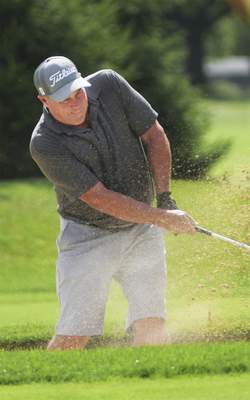 Katie Fyfe | The Journal Gazette  Mike Davis hits out of the sand trap at the eighth hole during the Senior City Golf Championship at Coyote Creek Golf Club on Sunday.