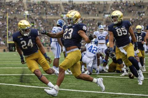 Courtesy | Atlantic Coast Conference  Notre Dame running back Kyren Williams (23) celebrates a second-half touchdown with teammates Tommy Tremble (24) and George Takacs (85).