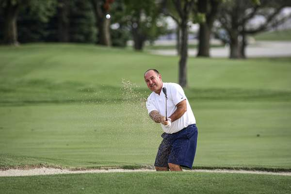 Mike Moore | The Journal Gazette Andy Rang fights his way out of a sand trap on Monday during the Senior City Golf Tournament championship at Coyote Creek Golf Club.