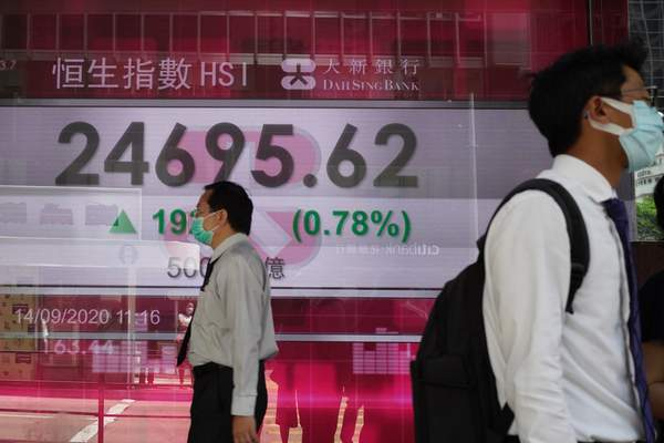 People walk past a bank's electronic board showing the Hong Kong share index at Hong Kong Stock Exchange Monday, Sept. 14, 2020. (AP Photo/Vincent Yu)