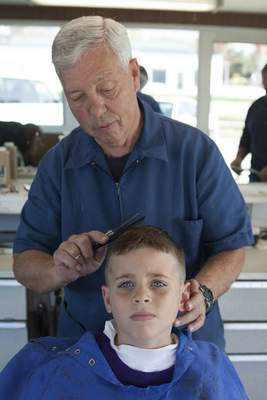 Carcione cuts his grandson Michael Carcione's hair in 2011. While the cuts for his grandchildren were free, he'd joke it was part of their inheritance.