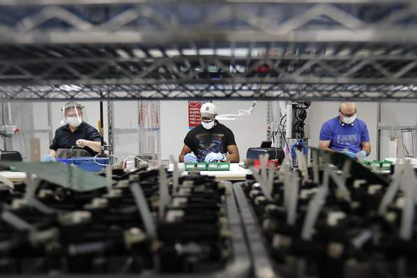 FILE - In this May 13, 2020, file photo, Ford Motor Co., line workers put together ventilators that the automaker is assembling at the Ford Rawsonville plant in Ypsilanti Township, Mich. (AP Photo/Carlos Osorio, File)