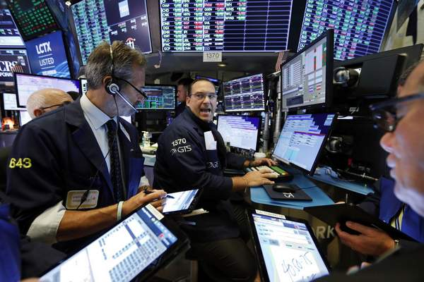 FILE - In this Aug. 21, 2019, file photo, specialist Anthony Matesic, center, works with traders at his post on the floor of the New York Stock Exchange. (AP Photo/Richard Drew, File)