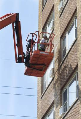 Katie Fyfe | The Journal Gazette A worker in a crane fixes up the outside of Westberry Apartments downtown Tuesday.
