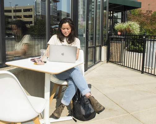 Michelle Davies | The Journal Gazette Purdue University Fort Wayne theater student Bella Hadley of Fort Wayne works on homework Tuesday morning outside the Conjure Coffee shop at Foellinger-Freimann Botanical Conservatory.
