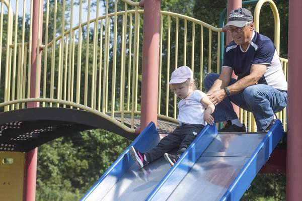 Michelle Davies | The Journal Gazette Dave Reas of Fort Wayne helps his granddaughter Jaysa Yenna, 2, carefully navigate a slide Tuesday afternoon at Foster Park.