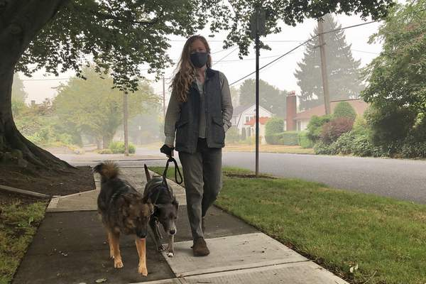 Associated Press Zoe Flanagan walks her dogs in Portland, Ore., one of many communities across the West blanketed by a wildfire-fueled haze.