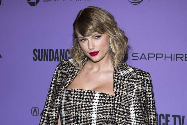FILE - In a Jan. 23, 2020 file photo, Taylor Swift attends the premiere of Taylor Swift: Miss Americana at the Eccles Theater during the 2020 Sundance Film Festival in Park City, Utah. Swift is coming back to her roots with a performance at this year's Academy of Country Music Awards. The nine-time ACM award winner will perform from the Grand Ole Opry House in Nashville, Tennessee, where the awards show will be broadcast Wednesday, Sept. 16, 2020 on CBS. (Photo by Charles Sykes/Invision/AP, File)