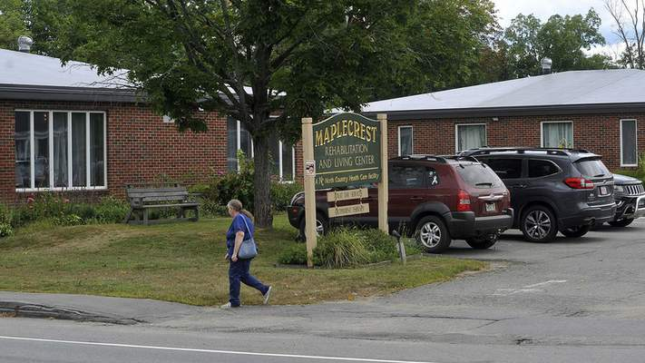 In this Aug. 19, 2020, photo, a pedestrian walks past the Maplecrest Rehabilitation and Living Center shown in Madison, Maine. (Rich Abrahamson/The Central Maine Morning Sentinel via AP)