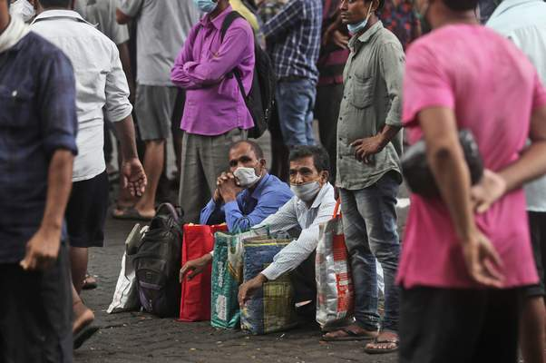 Daily wage laborers wait to get hired for the day in Mumbai, India, Wednesday, Sept. 16, 2020. India's total of coronavirus infections passed 5 million Wednesday, still soaring and testing the feeble health care system in tens of thousands of impoverished towns and villages. (AP Photo/Rafiq Maqbool)