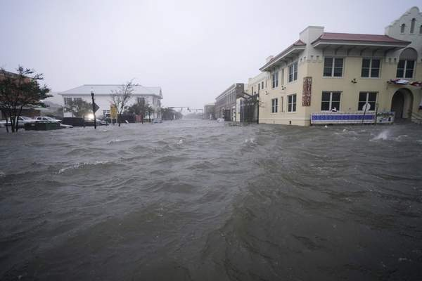 Flood waters move on the street, Wednesday, Sept. 16, 2020, in downtown Pensacola, Fla. (AP Photo/Gerald Herbert)