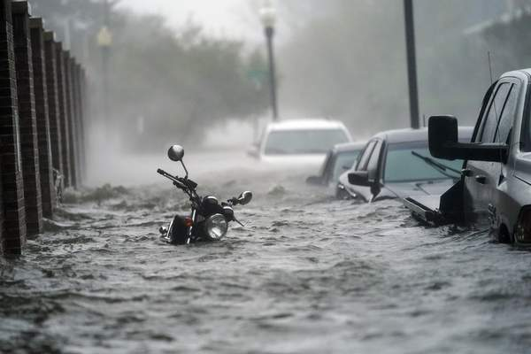 Flood waters move on the street, Wednesday, Sept. 16, 2020, in Pensacola, Fla. (AP Photo/Gerald Herbert)