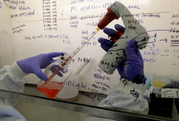 FILE - In this July 30, 2020 photo, Kai Hu, a research associate transfers medium to cells, in the laboratory at Imperial College in London. Imperial College is working on the development of a COVID-19 vaccine. (AP Photo/Kirsty Wigglesworth)