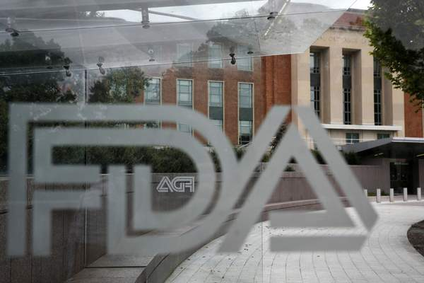 FILE - This Aug. 2, 2018, file photo shows the U.S. Food and Drug Administration building behind FDA logos at a bus stop on the agency's campus in Silver Spring, Md. (AP Photo/Jacquelyn Martin, File)