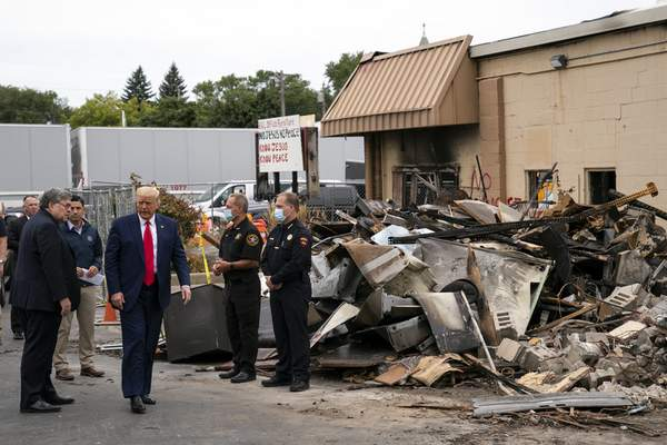 President Donald Trump walks Tuesday, Sept. 1, 2020, as he tours an area damaged during demonstrations after a police officer shot Jacob Blake in Kenosha, Wis. At left is Attorney General William Barr and acting Homeland Security Secretary Chad Wolf. (AP Photo/Evan Vucci)