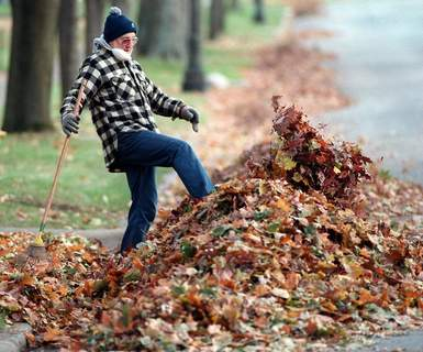 Nov. 14, 1995:Cal Armstrong kicks leaves away from a street gutter in front of his Foster Parkway home so water can flow through. (Journal Gazette file photo)