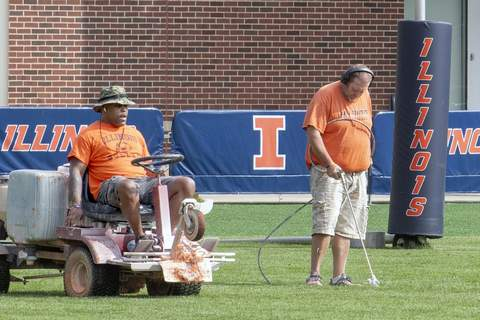 Big Ten Virus Outbreak Football Associated Press University of Illinois athletic facility attendants Tyrone Washington, left, and Shawn Hannan renew the line markers of the practice field Wednesday in Champaign, Ill. (Robin ScholzMBO)