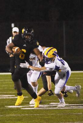 Katie Fyfe | The Journal Gazette Snider junior Tyrese Brown runs the ball down the field while Homestead junior Austin Keezer goes to tackle him during the third quarter at Spuller Stadium on Friday.