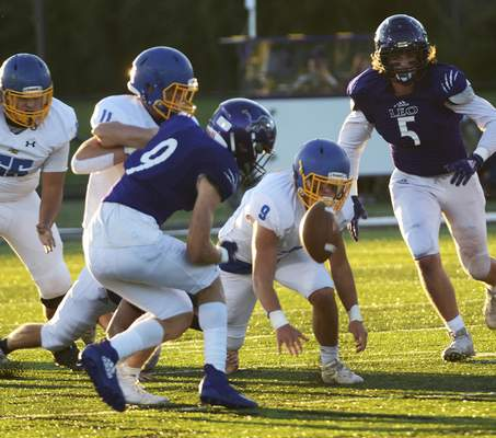 Katie Fyfe | The Journal Gazette  Leo and East Noble football teams players scramble for a wayward football Friday night at Leo.
