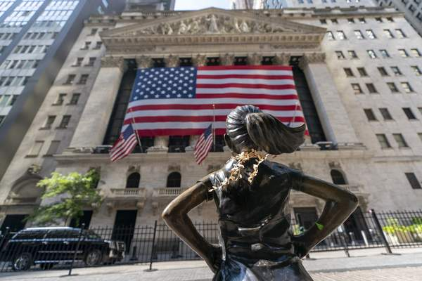 """Associated Press The """"Fearless Girl"""" bronze sculpture casts her eye toward the New York Stock Exchange, where stocks fell Monday as part of a global tumble rooted in worries about tougher coronavirus restrictions."""