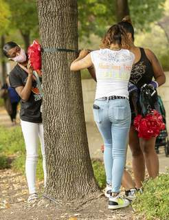 Rachel Bellwood | The Journal Gazette  Families hang red and black ribbons Thursday in Headwaters Park in honor of National Day of Remembrance for Murder Victims. (RACHEL BELLWOOD)