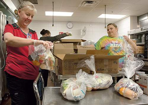 Michelle Davies | The Journal Gazette Jennifer Wiehe, left, and Jody Richardson, right, bag cold food items for prepacked lunches for Northwest Allen County Schools students in April.